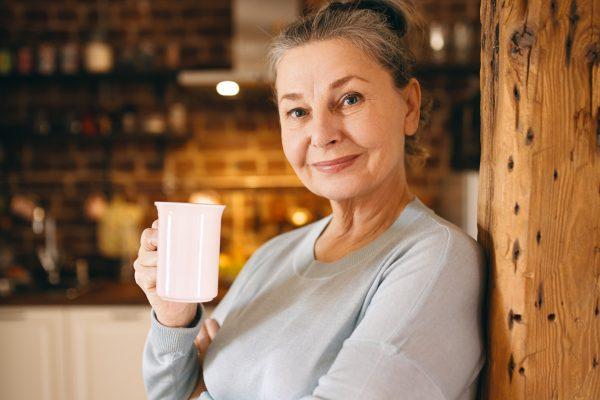 attractive-joyful-elderly-woman-posing-indoors-enjoying-hot-fresh-coffee-from-cup-morning